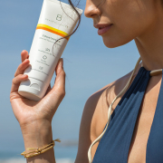 girl holding sunscreen benefits to wearing sunscreen