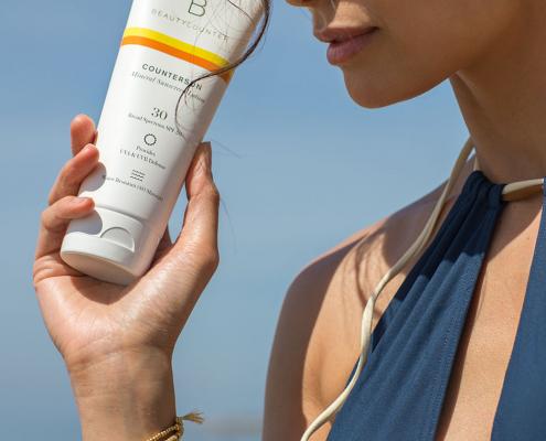 girl holding sunscreen benefits to wearing sunscreen